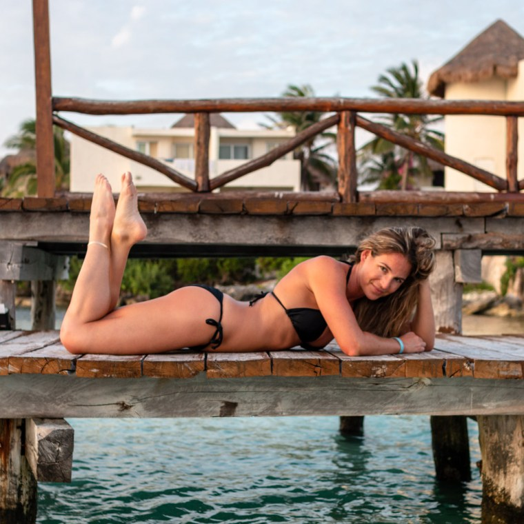 Corky, in a black bikini, poses on a wooden dock in Isla Mujeres, Mexico. Photo by Christopher Keelty.