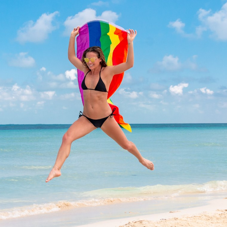 Model Corky, in a black bikini, runs up the beach with a rainbow gay pride flag. Photo by Christopher Keelty.