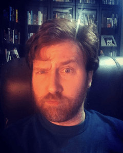 Photo of Christopher Opyr withone eyebrow raised, sitting in front of a bookshelf backdrop.