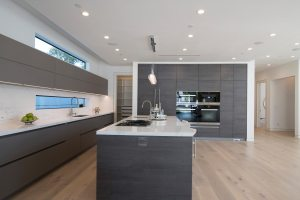 Dark oak handleless modern kitchen with white countertops, wall ovens and wood floors.