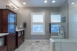 Transitional vanity with linen cabinet and custom frameless shower enclsoure, moroccan Porcelanosa tile.