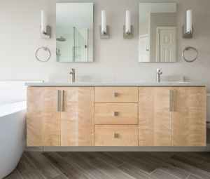 Wall hung maple vanity with center drawers and grey quartz countertop and freestanding tub.