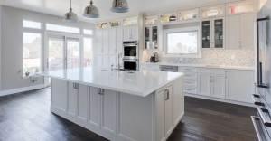 Transitional white Hallmark kitchen cabinets with dark flooring and polished nickel Waterstone fixtures.
