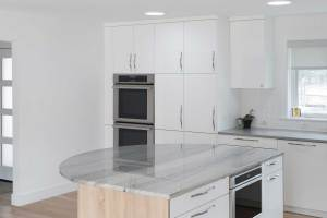 Round kitchen island in a modern German kitchen remodel in Littleton, CO with high-gloss white cabinets.