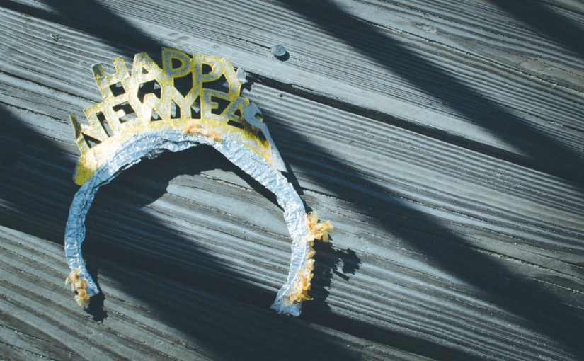 A crumpled Happy New Year crown on a wooden deck