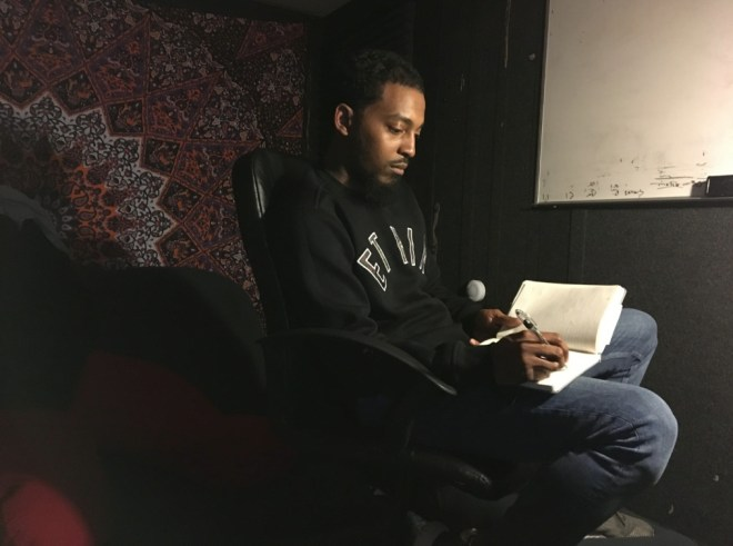 Rapper Chill Moody is pictured writing in his notebook after our interview. The picture is shadowy and introspective