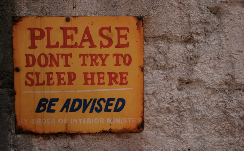 "Metal sign on a wall that says ""Please don't sleep here"""