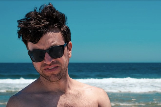 Close up of Stephen, with wind in his hair and a serious look hidden by sunglasses