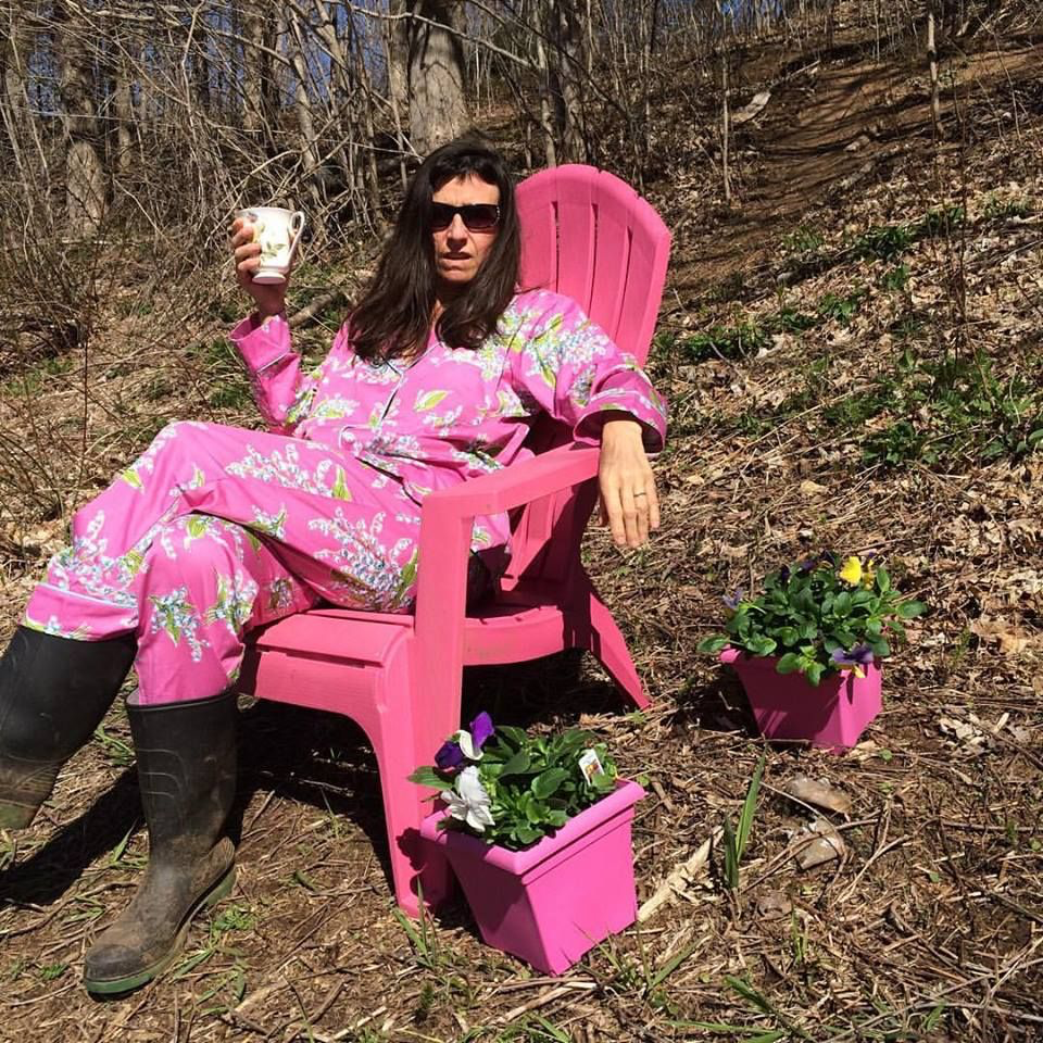 writer in pink pjs with coffee sitting in pink lawn chair