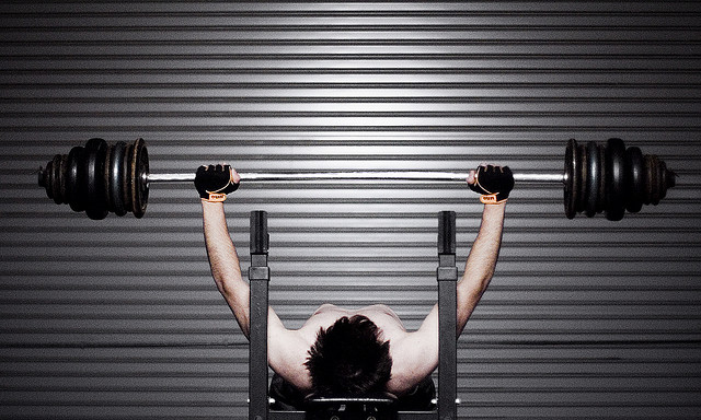 Pumping iron - young man weight lifting - protein requirements