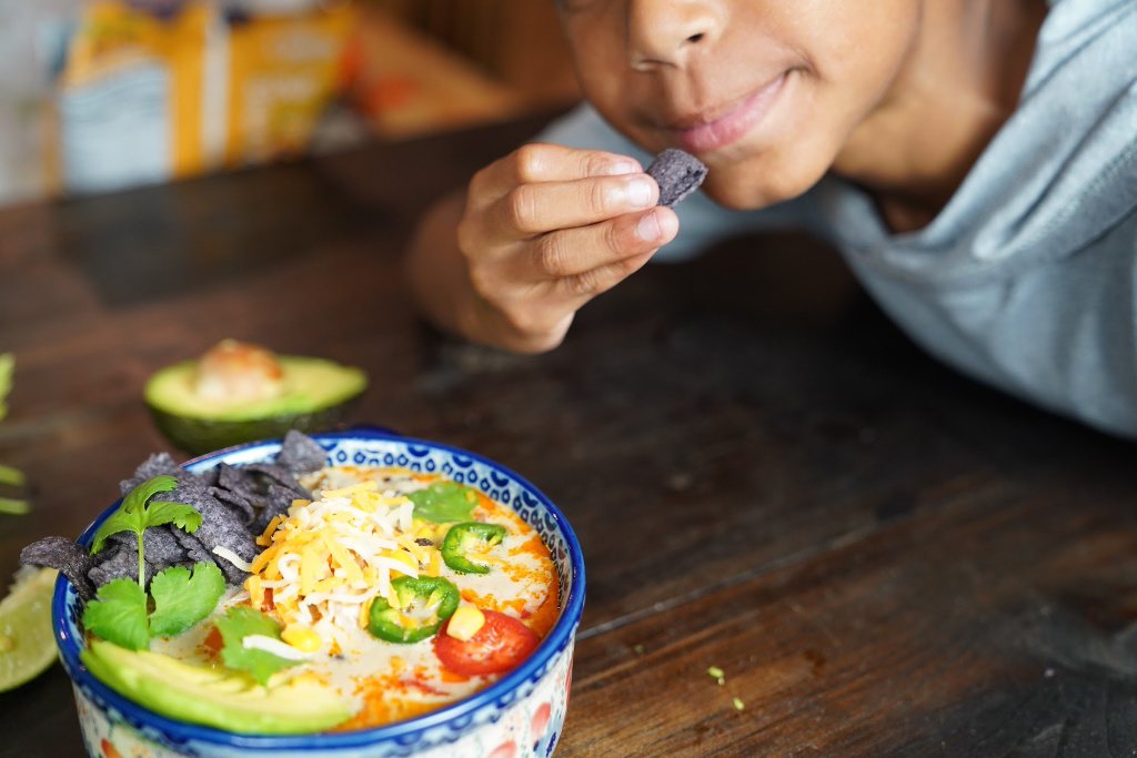child eating tortilla out of the chicken tortilla soup bowl