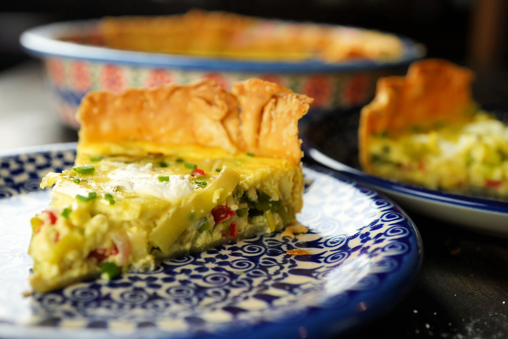 Leek asparagus and goat cheese quiche on blue plate