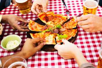 people holding sliced pizza
