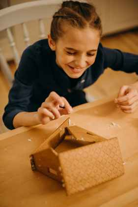 smiling girl making house from crackers