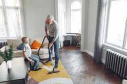 cheerful father talking with son while vacuuming