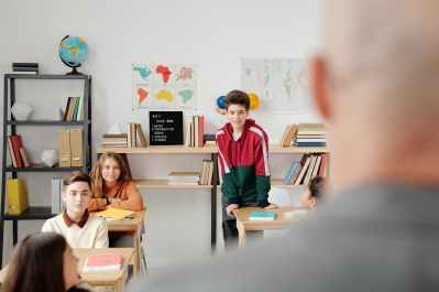 boy in red and green hoodie standing in the classroom