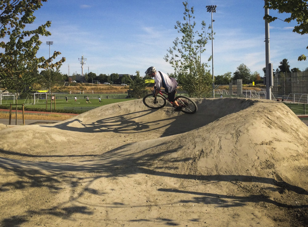 A rider cruises around the lower berm to build speed to get back up to the top of the track.