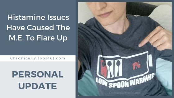 "Char is pointing to her shirt which shows an empty battery with the words ""low spoon warning"" on it. Title reads: Histamine issues have caused the M.E. to flare up. personal update."
