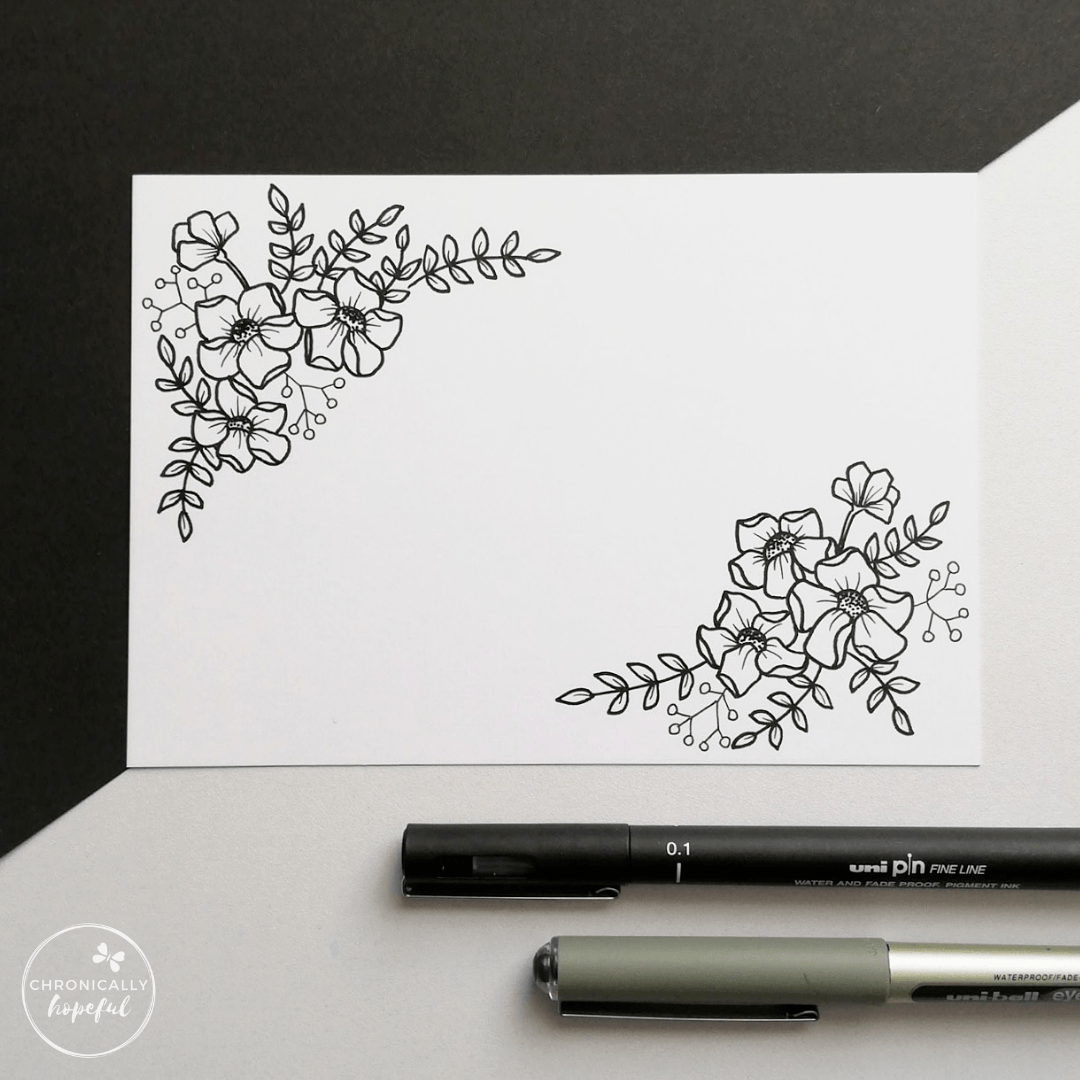 A white card with black botanical drawing, two pens positioned below the card on the table.