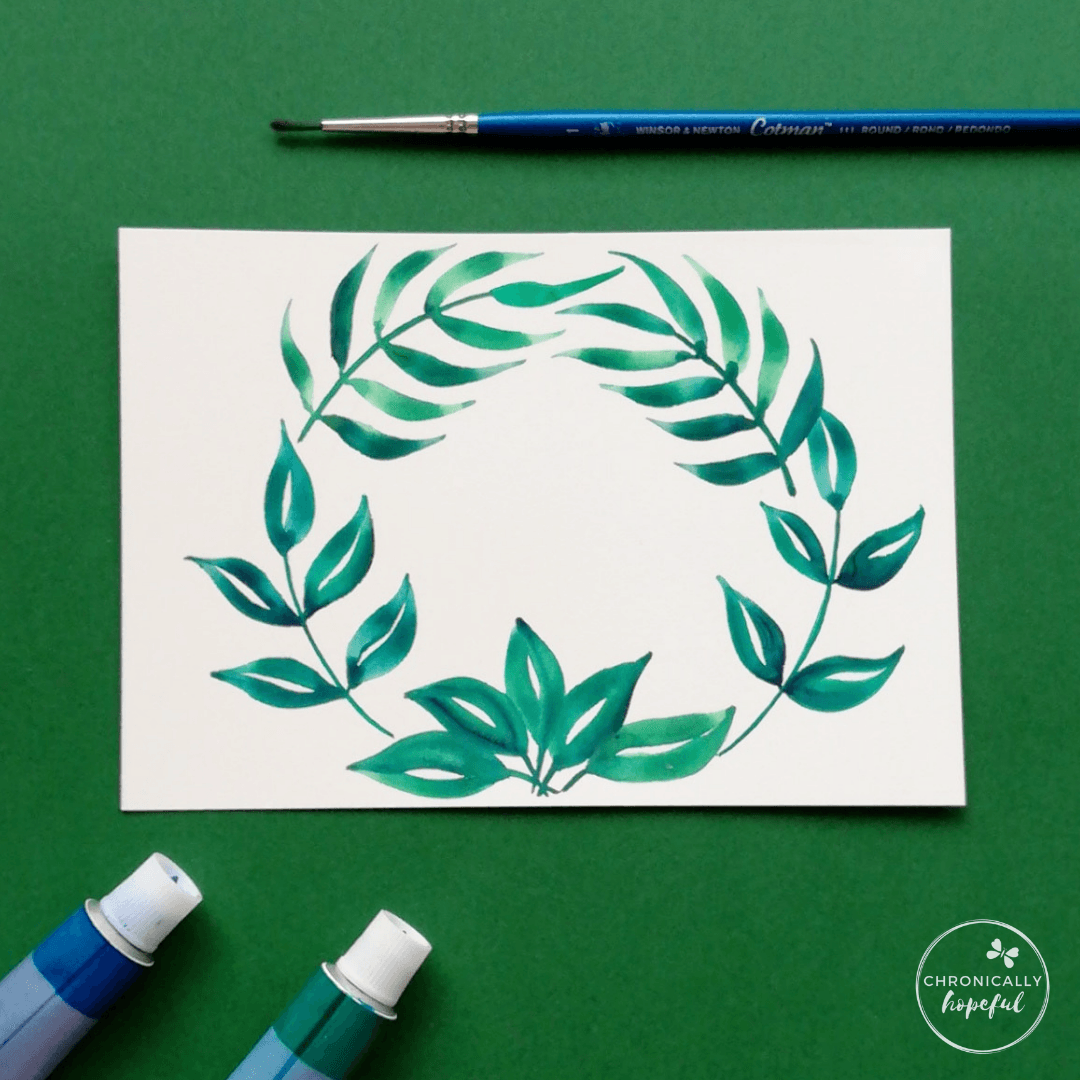 Leafy green watercolour wreath on white card, paint tubes and brush on table around the card