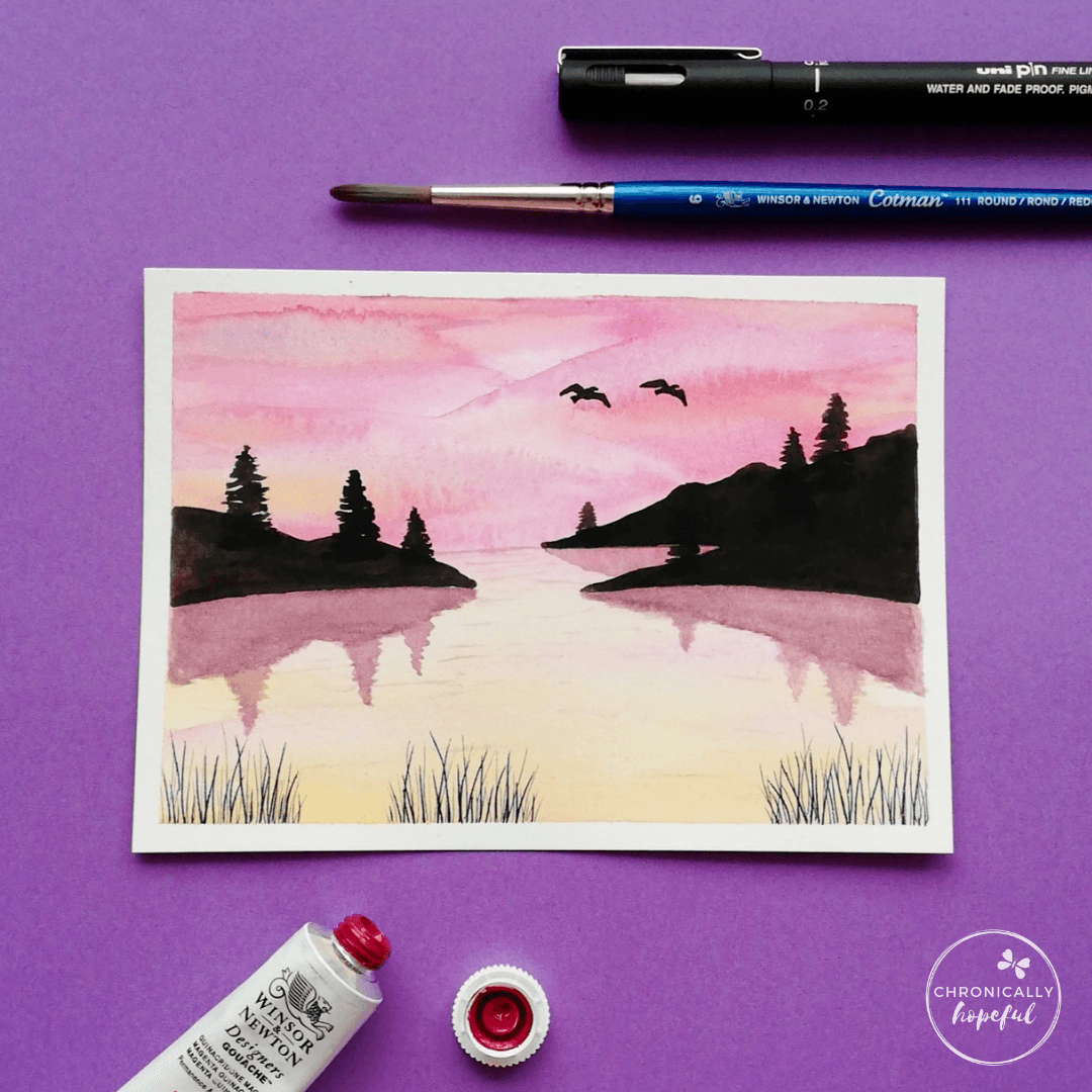 Sunset lake and mountains scene, with 2 birds flying in the sky and fine whispy grass in the foreground. Paint, brush and pen lyingon ht table around the card. by Chronicaly Hopeful Char