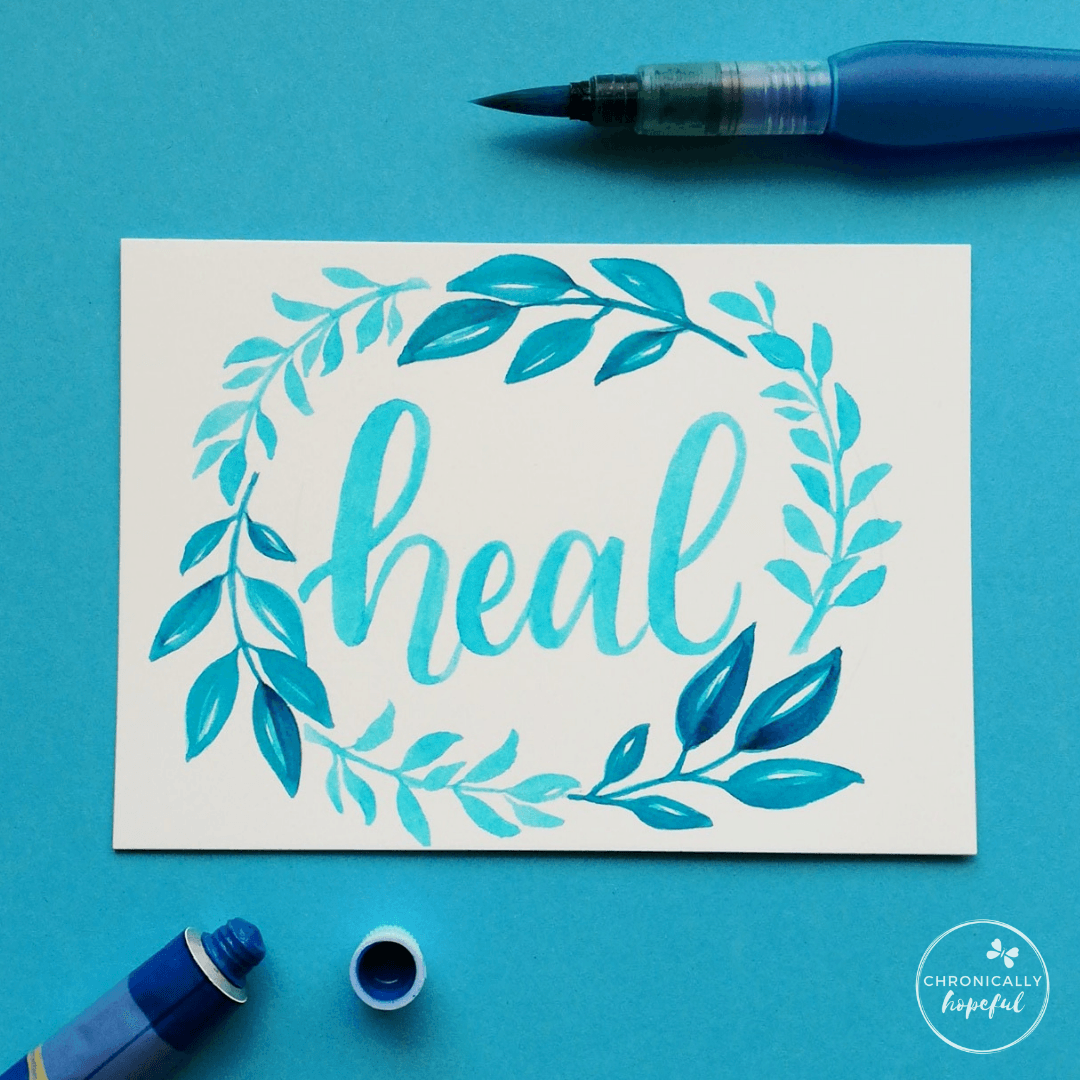 The word heal lettered in blue watercolour framed by a blue leafy wreath painted on white card by Chronically Hopeful Char