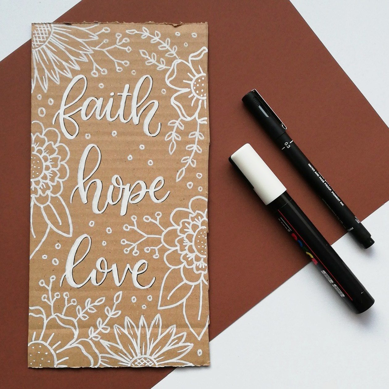 A piece of cardboard on a table with the words Faith, Hope Love lettered in white paint with botanical drawings around it. 2 pends on teh table next to the card.