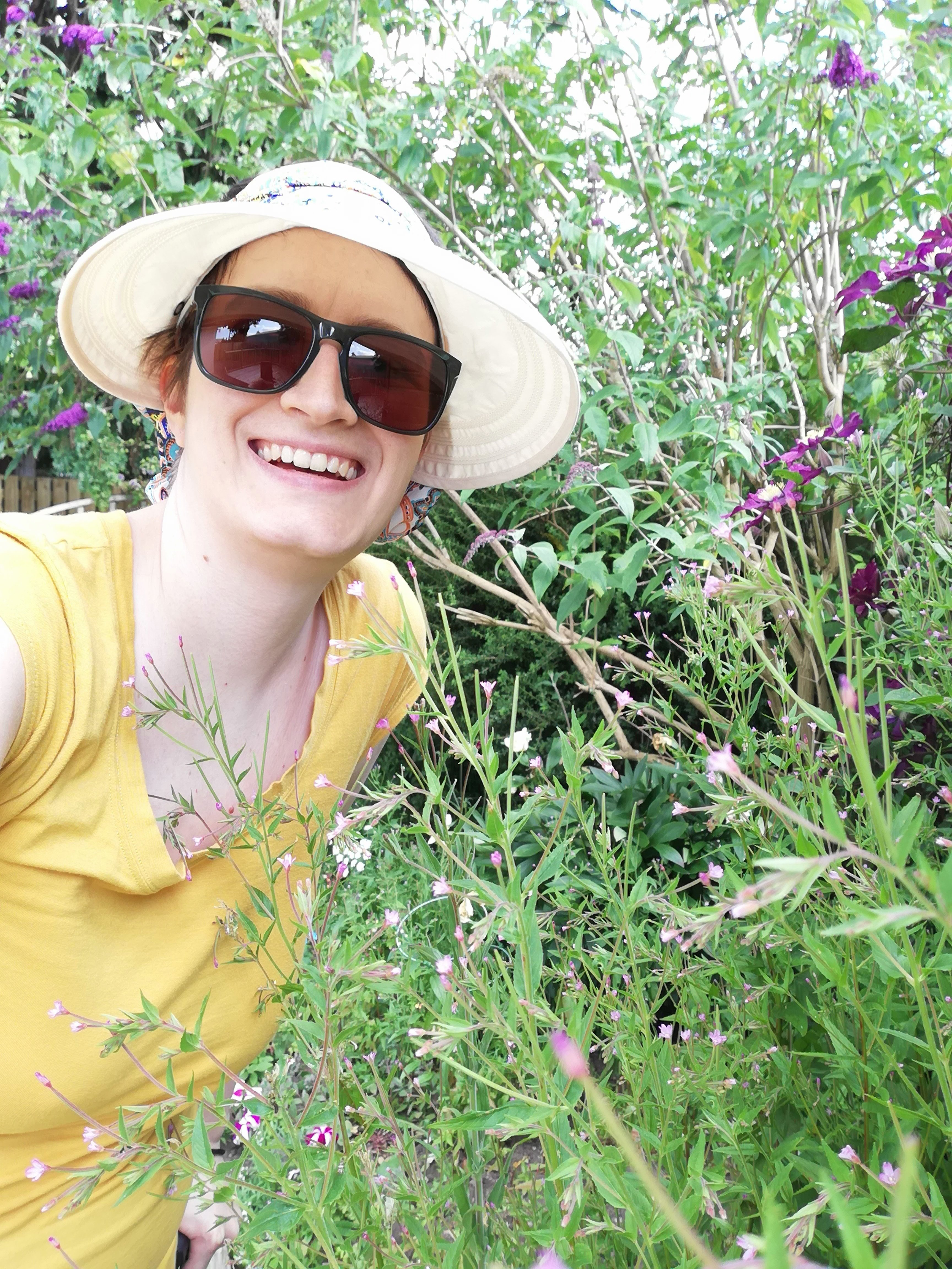 Char in the garden among the flowers. Wearing a sunhat and sunglasses.