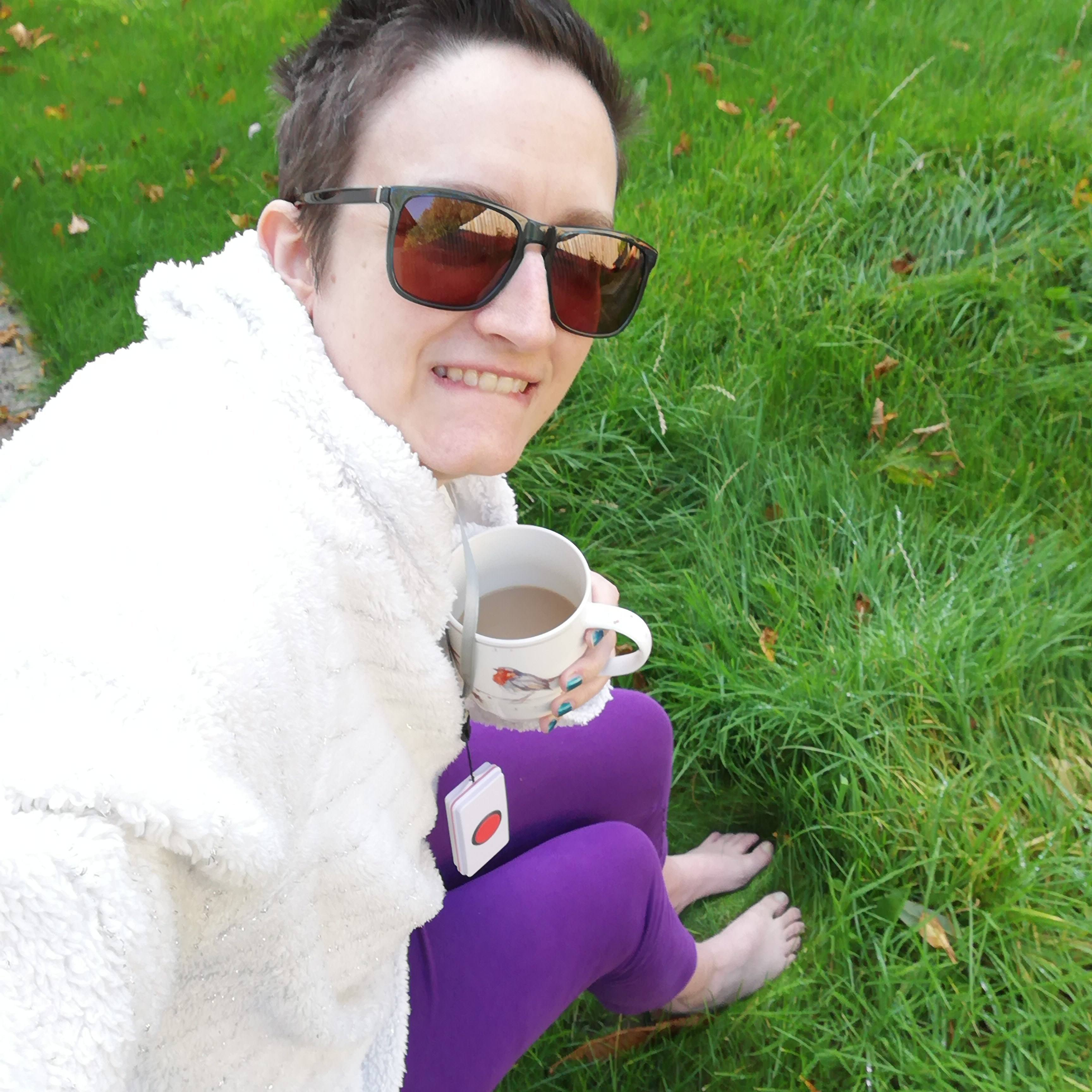 Char is sitting outside with a mug of coffee, her bare feet are on the grass.