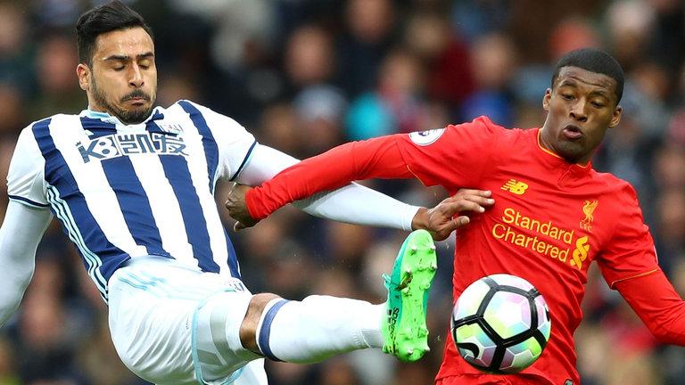 Nacer Chadli and Georginio Wijnaldum of Liverpool battle for possession