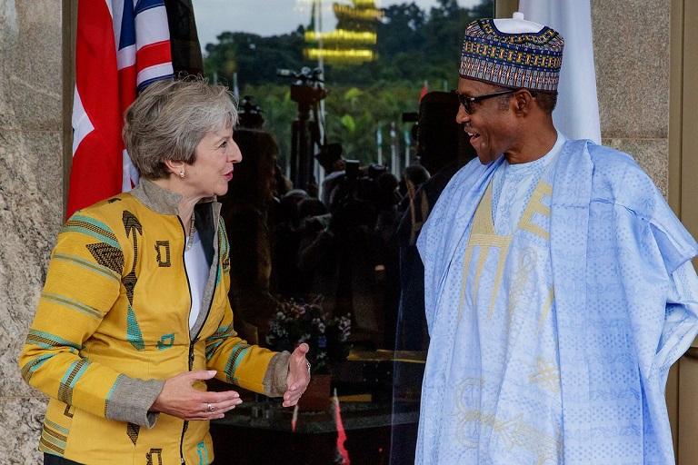UK Prime Minister Theresa May shares a joke with President Muhammadu Buhari on arriving Nigeria