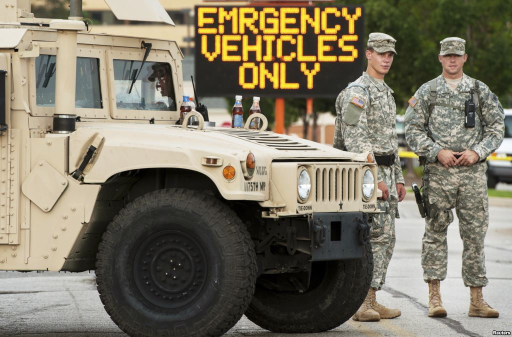 Roanoke County Va. police officers cower behind one of only four humvees.