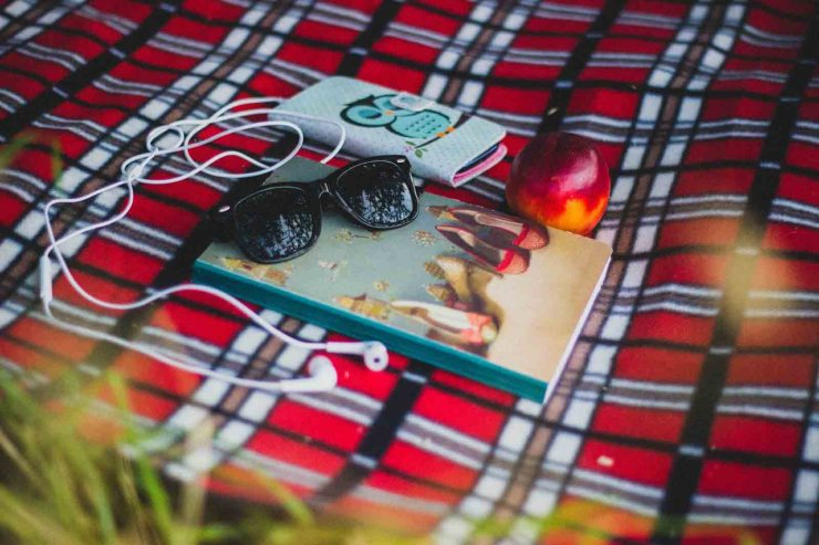 The scene contains a pair of black framed sunglasses sitting on a journal that has a photo of shoes on the cover.  The journal is laying on a red and black tartain picnic blanket.  There is also a mobile phone in a case with a cute cartoon owl print on the front and white earbud earphones snaking across the blanket near the journal.  There is also a nectarine beside the journal.