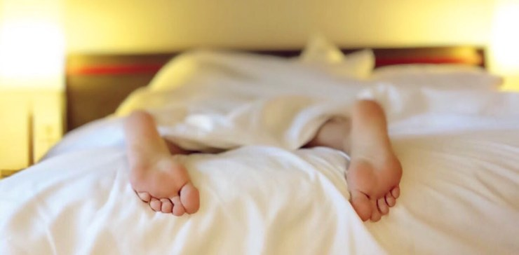Image focuses on the soles of someones bare feet sticking out from the end of a bed that has white sheets.  The person must be lying on their stomach as the toes face downwards.  There is a blurred lamp lighting the scene from the left of the bedhead.