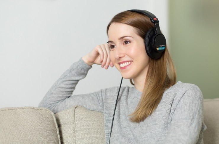 Smiling lady with light brown hair sitting on a cream coloured couch wearing a grey jumper. She is looking into the distance smiling with her arm resting on the back of the couch and her hand on her cheek. She is wearing over ear headphones.