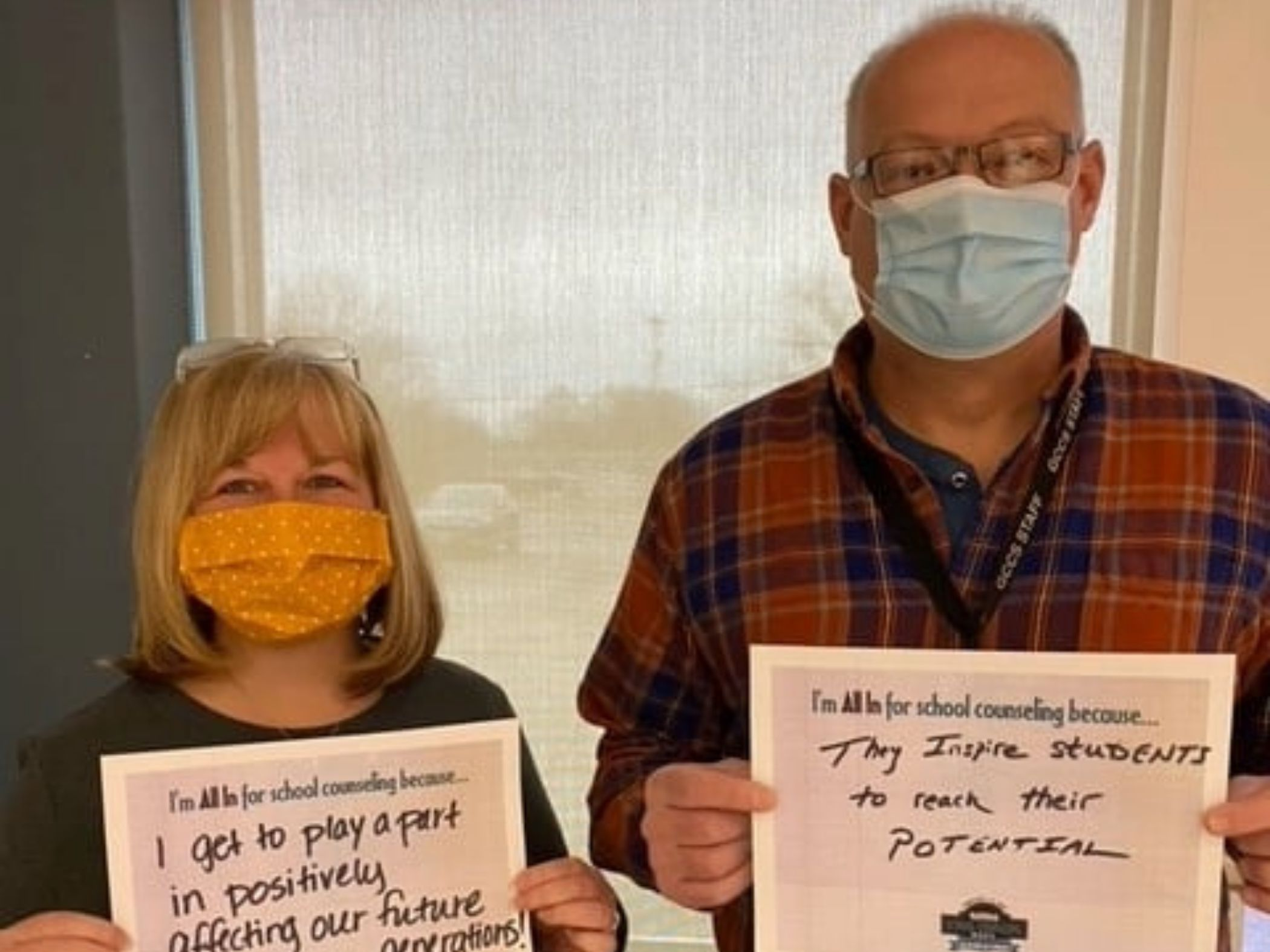 Staff members posing with signs saying why they are all in for school counseling