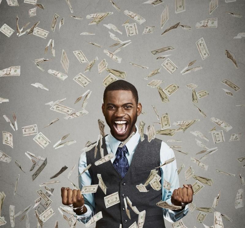 happy man pumping fists celebrates success under money rain