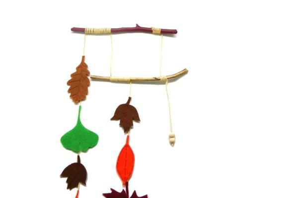 Adorno colgante otoñal hecho con ramas secas y hojas de fieltro de colores