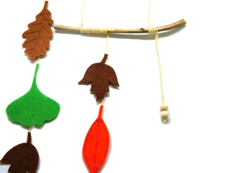 adorno colgante otoñal hecho con ramas secas y hojas de fieltro