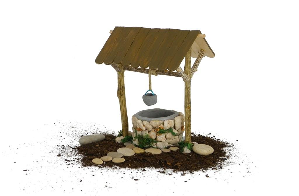 figura en miniatura de un pozo para la decoracion del nacimiento hecha con plastilina, ramas secas, palos planos y piedras pequeñas