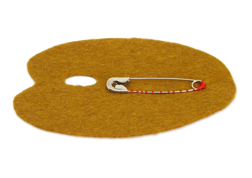 pieza de fieltro color marron con un imperdible cosido para hacer broche de una paleta de pintor