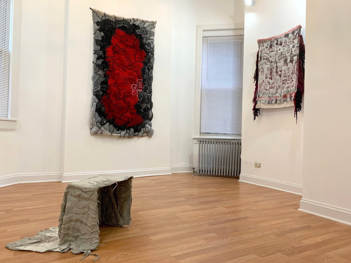 3 textiles artworks, 2 hanging from adjacent walls, and 1 on the floor