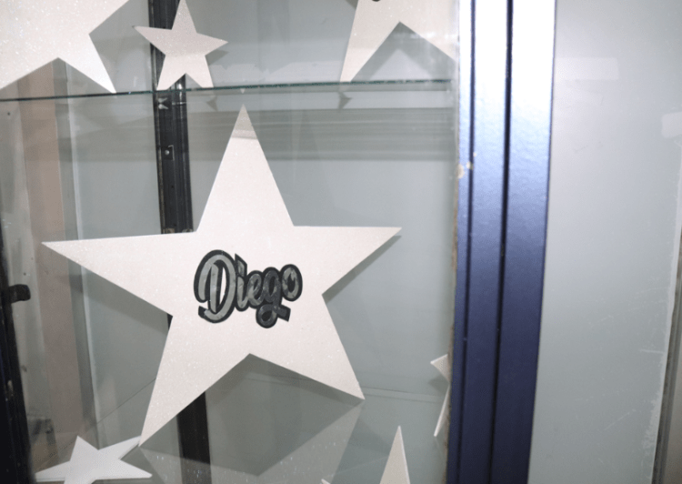 "Close up photo of a glass cabinet focusing in on a paper star with a sticker text stating ""Deigo""."