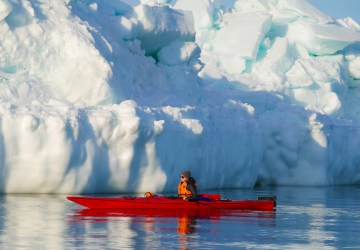 Guide Jody Steeves slips through the calm waters of Hudson Bay in a kayak on Churchill Wild's Journey to the Floe Edge safari