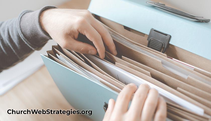 hands flipping through files in a folder