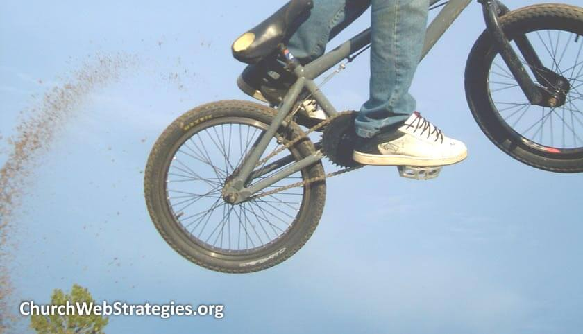 boy riding bicycle off a jump