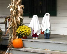 Hai bé ma bên thềm nhà chào đón người đi ngang.
