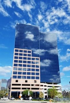 Nhà cao tầng bên cạnh cơ quan làm việc của tôi. Hôm ấy trời nhiều mây rất đẹp. Mây như khói bay lang thang. Mây bay vào và ở lại trong những bức tường kính.