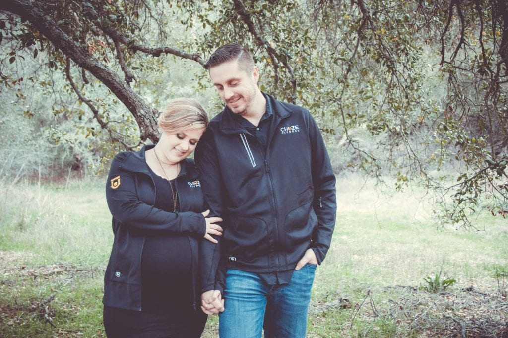 Team Members, Nathan and Julia Muzquiz, wearing their Chuze Fitness jackets for their maternity photos.