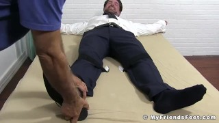 Tied up businessman in a suit tickled all over his feet